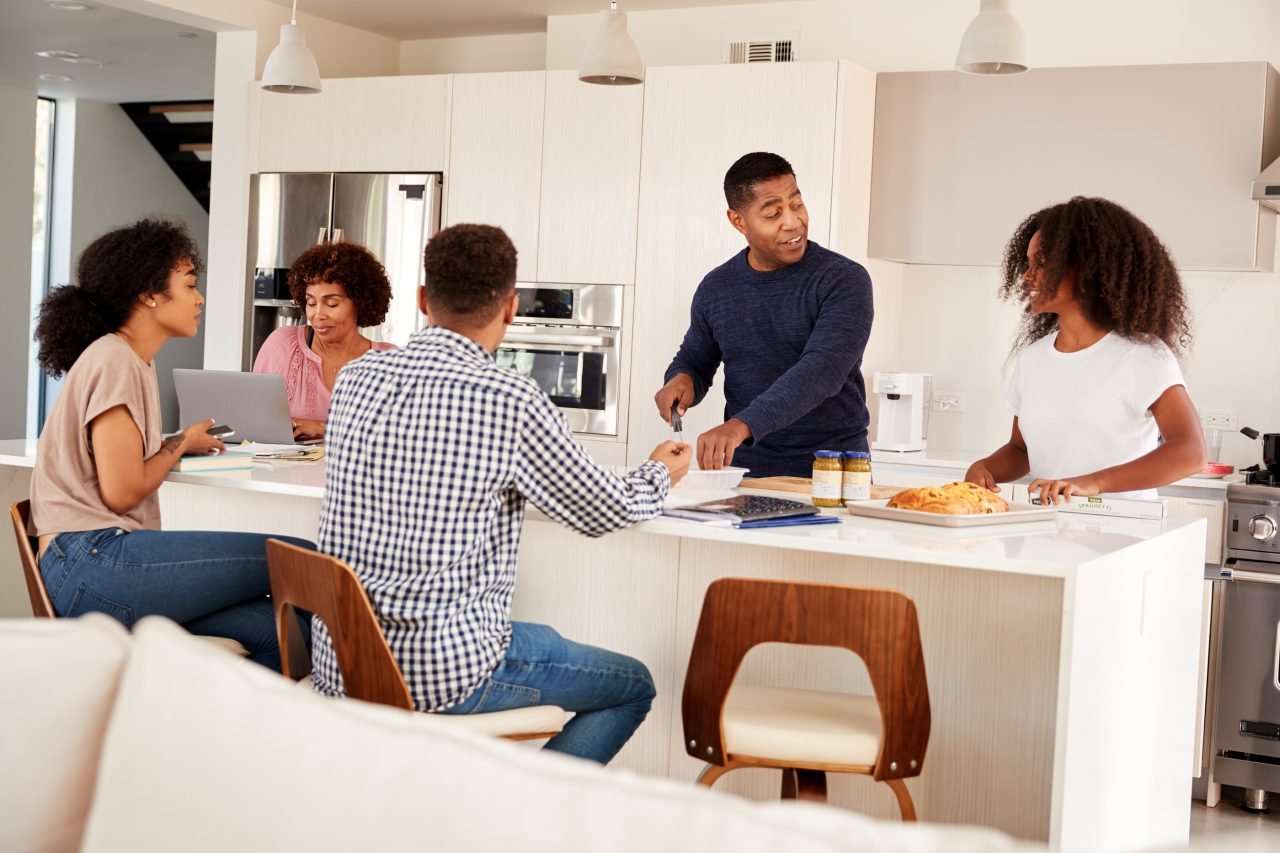 A photo of a family talking about mental health in the kitchen before lunch.